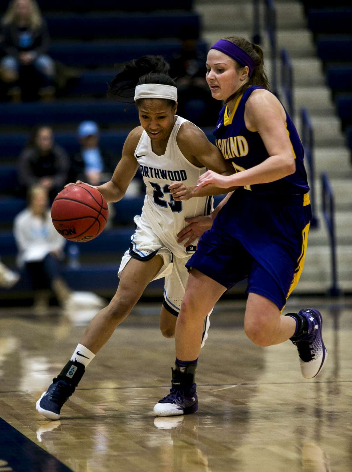 Northwood's Zaikai Wells drives the ball as Ashland's Maddie Dackin blocks her as Northwood plays Ashland at Riepma Arena in Midland on Saturday, Jan. 20, 2018. (Josie Norris/for the Daily News)