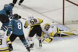 San Jose Sharks center Tomas Hertl, top left, from the Czech Republic, scores a goal past Pittsburgh Penguins goalie Casey DeSmith (1) during the third period of an NHL hockey game in San Jose, Calif., Saturday, Jan. 20, 2018. (AP Photo/Jeff Chiu)