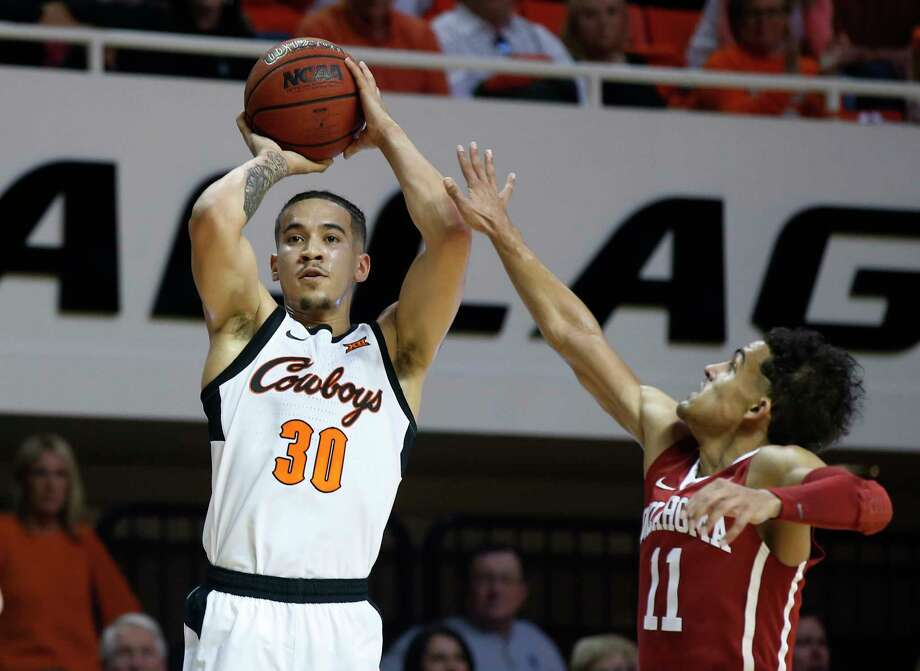 Oklahoma State guard Jeffrey Carroll (30) shoots in front of Oklahoma guard Trae Young (11) in the first half of an NCAA college basketball game in Stillwater, Okla., Saturday, Jan. 20, 2018. (AP Photo/Sue Ogrocki) Photo: Sue Ogrocki / AP2018