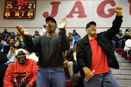 Central fans Johnny Bill, left, and Anthony Garrett cheer on the Jaguars during a boys basketball game against Ozen at Central on Friday night. The two men attended Charlton-Pollard.  Photo taken Friday 1/19/18 Ryan Pelham/The Enterprise