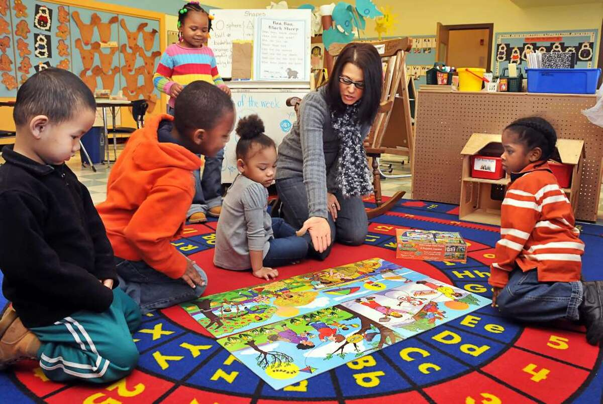 Giffen Memorial Elementary pre-kindergarten teacher Emilia Giorgio with students, from left, Na Reh, Justin Walker, Damarra McCall (background, standing), Nigianna Grimes and Shawn Johnson. ( John Carl D'Annibale / Times Union )