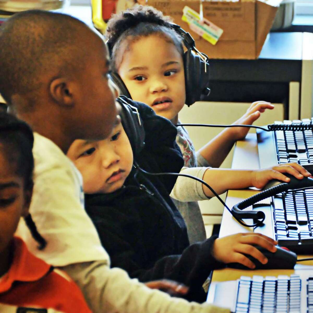 Giffen Memorial Elementary pre-kindergarten students, from left, Deavion Springsteen, Na Reh and Nigianna Grimes at computers in their classroom. (John Carl D'Annibale / Times Union)
