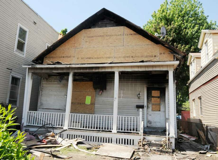 This house at 117 5th Ave. in Troy is boarded up and tagged by Code Enforcement as uninhabitable following a Sunday fire. (Luanne M. Ferris/Times Union) Photo: LUANNE M. FERRIS