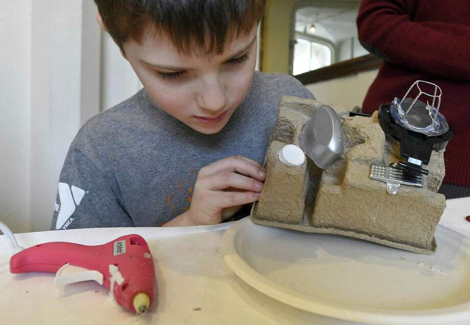 "Benjamin Berman, 8, of Stamford tinkers with the design of his creative sculpture of a camera he crafted during a Gerb-O-Matic Workshop: Make-and-Take Sculpting Event at the Stamford Museum & Nature Center in Stamford, Conn. on Saturday, Jan. 20, 2018. Sculptor Stephen Gerberich inspired and direct participants to sculpt their own mini-masterpieces from a smorgasbord of parts painstakingly culled from dumpsters, thrift shops, and dollar stores during Gerberich's nationwide travels. Handmade sculptures, assembled using hot glue ""welding"" by the children and adults into original works, while acquiring a new appreciation for the creative reuse of ordinary objects. Photo: Matthew Brown / Hearst Connecticut Media / Stamford Advocate"
