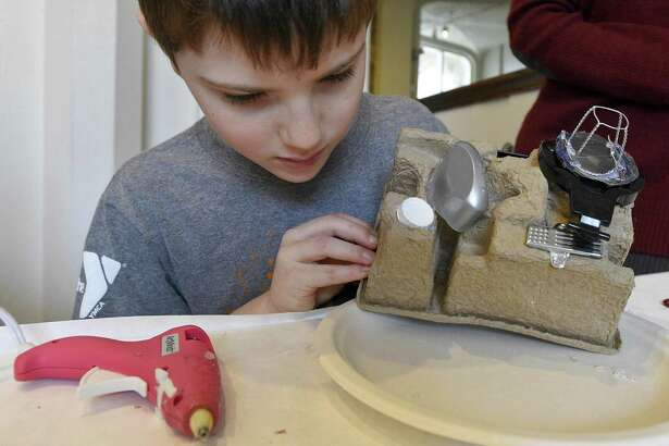 """Benjamin Berman, 8, of Stamford tinkers with the design of his creative sculpture of a camera he crafted during a Gerb-O-Matic Workshop: Make-and-Take Sculpting Event at the Stamford Museum & Nature Center in Stamford, Conn. on Saturday, Jan. 20, 2018. Sculptor Stephen Gerberich inspired and direct participants to sculpt their own mini-masterpieces from a smorgasbord of parts painstakingly culled from dumpsters, thrift shops, and dollar stores during Gerberich's nationwide travels. Handmade sculptures, assembled using hot glue """"welding"""" by the children and adults into original works, while acquiring a new appreciation for the creative reuse of ordinary objects."""