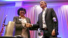 Democratic gubernatorial candidates Lupe Valdez, left, and Andrew White shake hands after take part in forum at Texas AFL-CIO's COPE convention at the Sheraton Austin hotel on Saturday, Jan. 20, 2018.