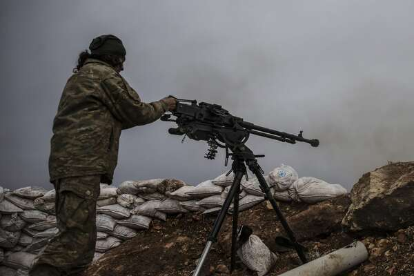 IDLIB, SYRIA - JANUARY 19: A member of the Free Syrian Army fires towards terrorist organizations PKK/PYD side in Idlib, Syria on January 19, 2018. (Photo by Onur Coban/Anadolu Agency/Getty Images)