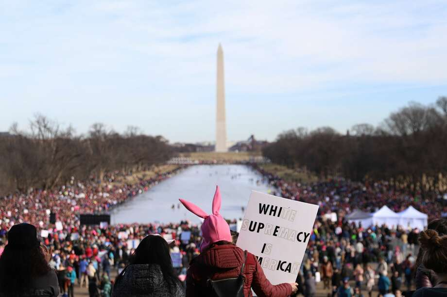 People gather at the Lincoln Memorial reflecting pool to rally before the Women's March on January 20, 2018 in Washington, D.C. Across the nation, people are marching on the one-year anniversary of President Trump's swearing-in to protest against his past statements on women and to celebrate women's rights around the world. Photo: Alex Wroblewski/Getty Images