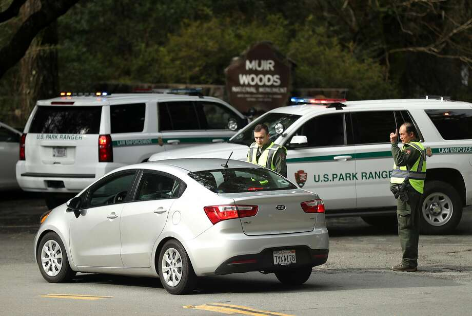Seth Williams (left) and Bob Airey  of the National Park Service advise visitors to Muir Woods National Monument in Mill Valley that the parking lots are closed. Photo: Scott Strazzante, The Chronicle