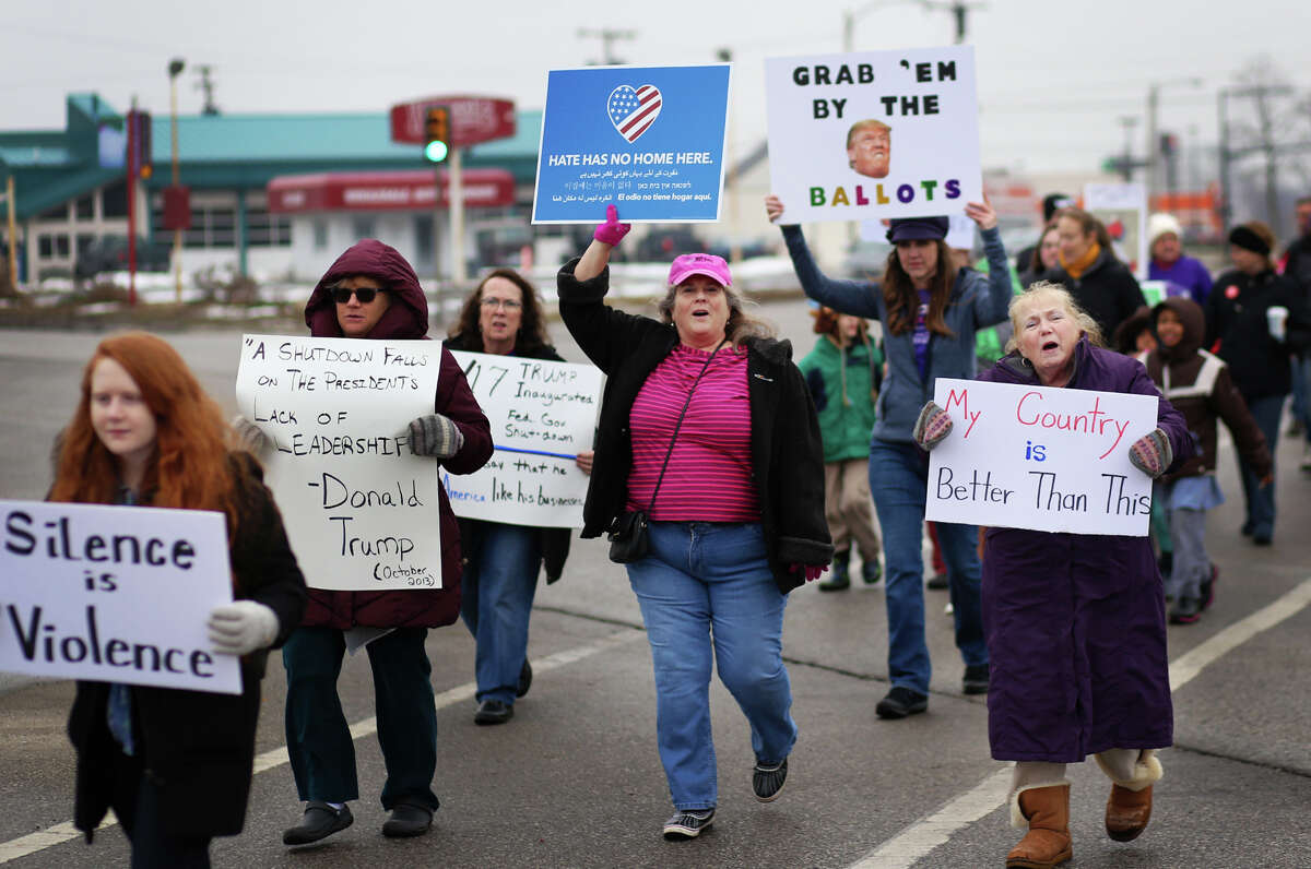 A group of over 300 people march and chant near the intersection of Washington and South Saginaw during the worldwide Women's March protest on Sunday, Jan. 21, 2018. (Samantha Madar/for the Daily News)