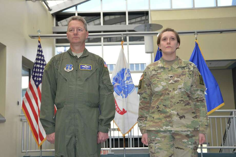 Army National Guard Staff Sgt. Melanie Groff stands at attention with Maj. Gen. Anthony German, the adjutant general of the New York National Guard, before she received a Meritorious Service Medal at State Division of Military and Naval Affairs Headquarters in Latham. (Capt. Jean Marie Kratzer / Army National Guard)