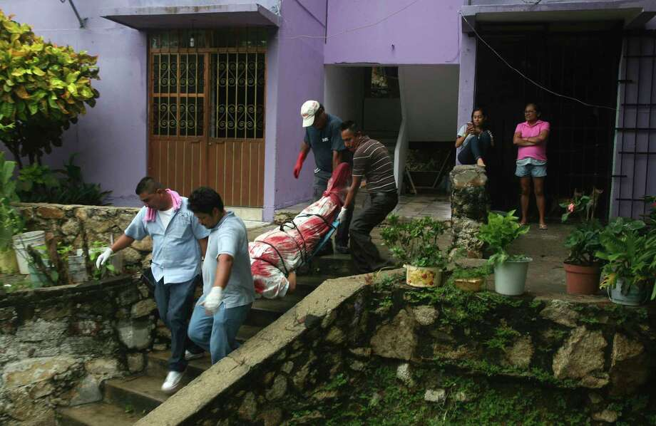 FILE - In this Aug. 29, 2017 file photo, a body wrapped in a bloodstained sheet is removed from an apartment building where a woman and two men were executed, in the Alta Progreso neighborhood of Acapulco, Mexico. Both men were bound with tape, and all three were shot in the head at an apartment outfitted as an office for a taxi service. Mexico's Interior Department posted on Sunday, Jan. 21, 2018 that the country's homicide rate is the highest in decades. (AP Photo/Bernandino Hernandez, File) Photo: Bernandino Hernandez, STR / Copyright 2017 The Associated Press. All rights reserved.