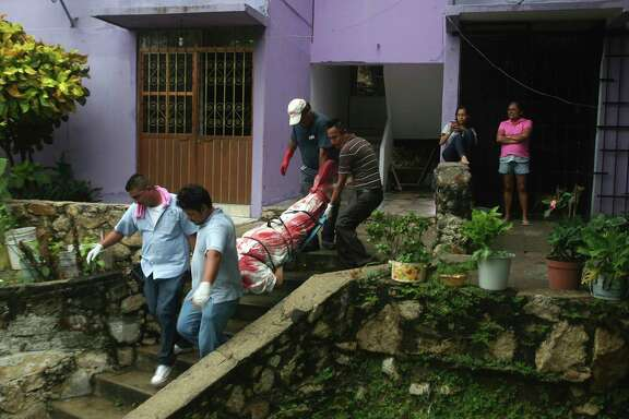 FILE - In this Aug. 29, 2017 file photo, a body wrapped in a bloodstained sheet is removed from an apartment building where a woman and two men were executed, in the Alta Progreso neighborhood of Acapulco, Mexico. Both men were bound with tape, and all three were shot in the head at an apartment outfitted as an office for a taxi service. Mexico's Interior Department posted on Sunday, Jan. 21, 2018 that the country's homicide rate is the highest in decades. (AP Photo/Bernandino Hernandez, File)