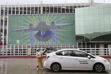 "With the ""¡Adelante San Antonio!"" mural as a back- drop, Linda Thomas drops off an airport traveler."