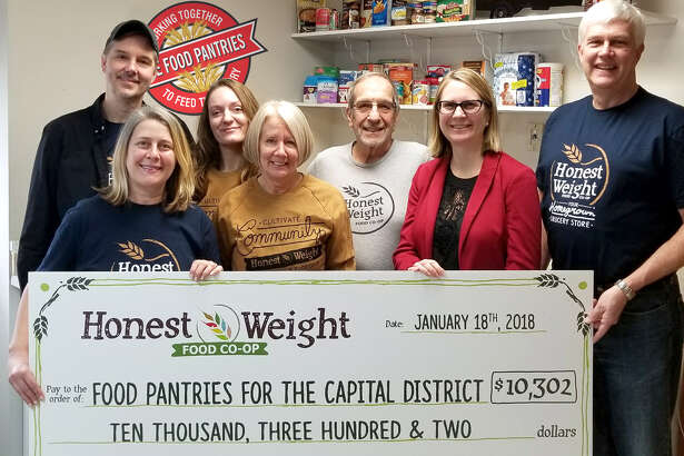 On Jan. 18, Honest Weight Food Co-op presented a check worth $10,302 to The Food Pantries for the Capital District in Albany. The funds are the result of a two-month long donation drive at the grocery store, where shoppers were asked to buy paper ?cans? for $1 each at checkout. Shown, from left, are Honest Weight Marketing Director John Akots, Outreach Coordinator Amy Ellis, Front End Assistant Manager Kelly Donegan, cashiers Debbie Foley and Al DeSalvo, Food Pantries Executive Director Natasha Pernicka and Honest Weight Chief Cooperative Officer Rick Mausert.