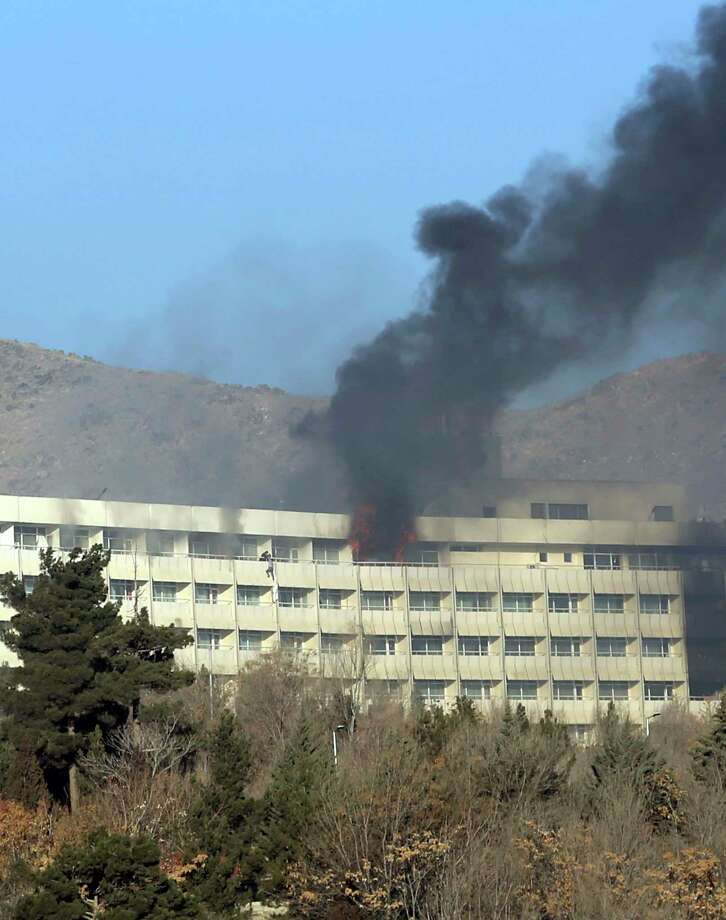Men try to escape from a balcony of the Intercontinental Hotel after an attack in Kabul, Afghanistan, Sunday, Jan. 21, 2018. Gunmen stormed the hotel and sett off a 12-hour gun battle with security forces that continued into Sunday morning, as frantic guests tried to escape from fourth and fifth-floor windows. (AP Photo/Rahmat Gul) Photo: Rahmat Gul / Copyright 2018 The Associated Press. All rights reserved.