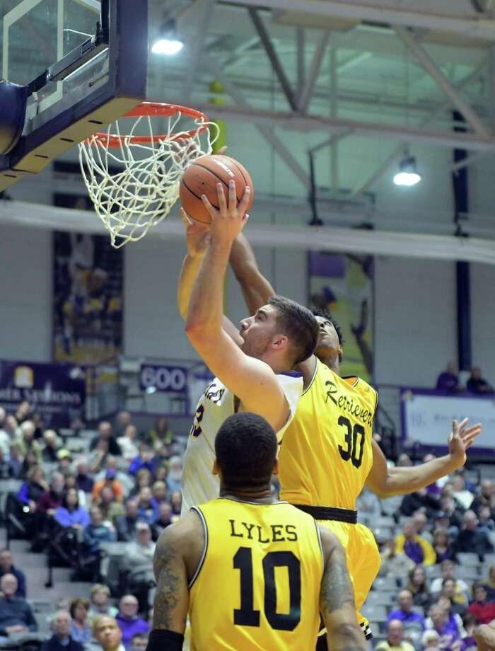 Greig Stire, left, of UAlbany puts up a shot as Daniel Akin of UMBC tries to block the shot during their game on Sunday, Jan. 21, 2018, in Albany, N.Y.    (Paul Buckowski/Times Union) Photo: PAUL BUCKOWSKI / (Paul Buckowski/Times Union)