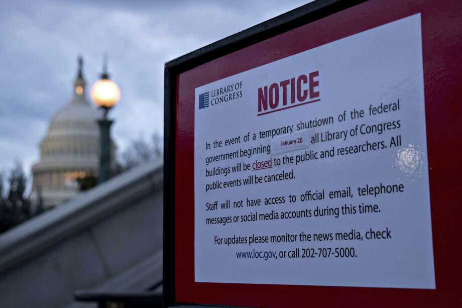 The U.S. Capitol stands past a temporary shutdown sign outside the Library of Congress in Washington on Jan. 21, 2018. Photo: Bloomberg Photo By Andrew Harrer. / © 2018 Bloomberg Finance LP