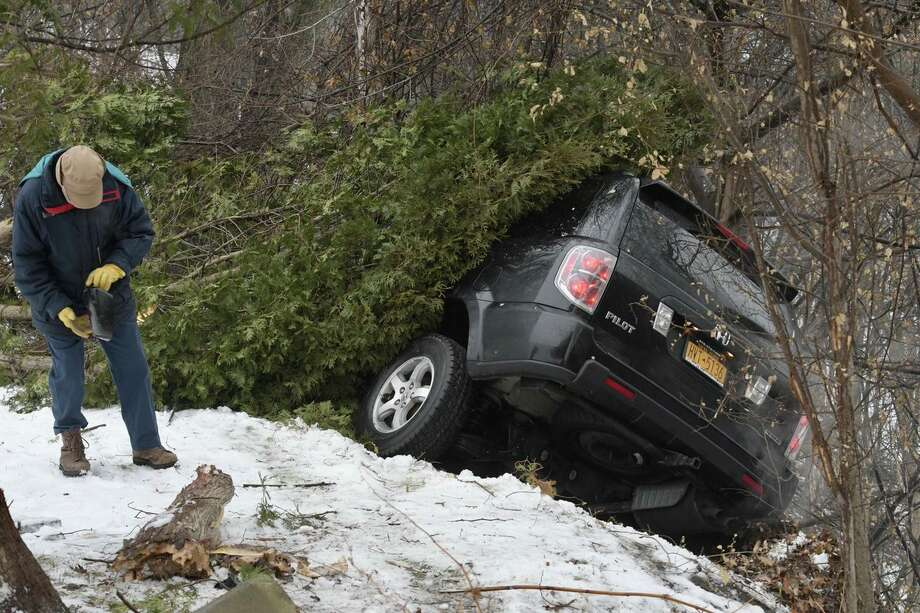 An SUV narrowly avoided sliding down a steep ravine in Rensselaer on Monday after it slid on ice and was stopped by trees. (Skip Dickstein/Times Union) Photo: Skip Dickstein/Times Union