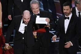 """FILE - In this Feb. 26, 2017, file photo, Jordan Horowitz, producer of """"La La Land,"""" left, shows the envelope revealing """"Moonlight"""" as the true winner of best picture at the Oscars in Los Angeles as presenter Warren Beatty and host Jimmy Kimmel, right, look on. The film academy and its accounting firm, PwC, are announcing a spate of new rules Monday, Jan. 22, 2018, meant to avoid an envelope gaffe like at last year's show, when """"La La Land"""" was mistakenly announced as the winner instead of """"Moonlight."""" PwC U.S. Chairman Tim Ryan said the new protocols include additional personnel and oversight, as well as practicing what to do if a presenter reads the wrong name. (Photo by Chris Pizzello/Invision/AP, File)"""
