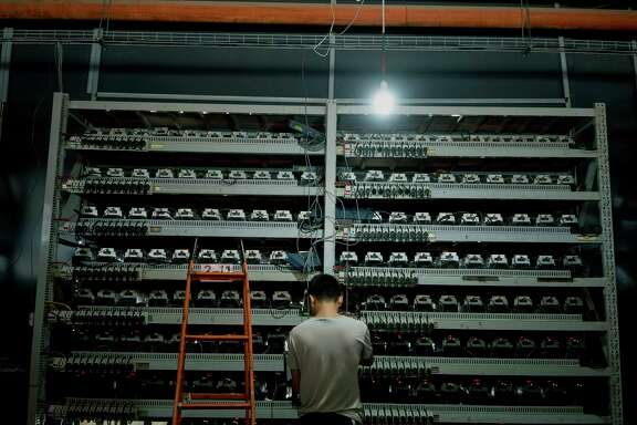 Li Shuangsheng, works at Bitmain, a Bitcoin farm in Dalad Banner, Mongolia, Aug. 11, 2017. Creating a single cryptocurrency token requires as much electricity as two yearsÕ worth of consumption by an average American home. (Giulia Marchi for The New York Times)