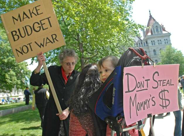 From left, OTDA employee Inez Haettenschwiller, of Albany, holds a sign and talks to Alicia Sullivan, of Sloansville, a lawyer for the state, at a protest against the governor's furlough plan. Alicia carries her 1-year-old daughter Alexandria on her back.(Lori Van Buren / Times Union) Photo: LORI VAN BUREN