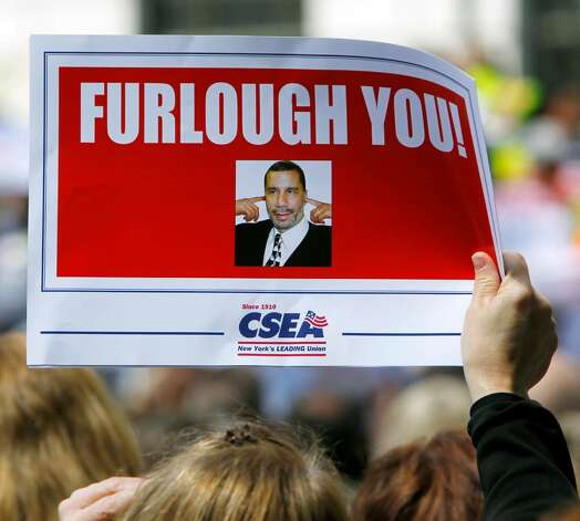 A state worker holds a sign during a rally against Gov. David Paterson's furlough plan outside the Capitol in Albany, N.Y., on Monday, May 10, 2010.  (AP Photo/Mike Groll) Photo: Mike Groll / AP