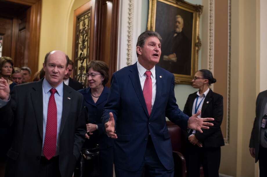 Sens. Joe Manchin, D-W.Va., right, Susan Collins, R-Maine, center, Chris Coons, D-Del., left, and others leave the Senate floor in the Capitol after they passed a continuing resolution to reopen the government on January 22, 2018. Photo: Tom Williams/CQ-Roll Call, Inc.