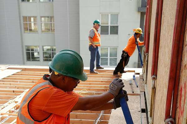 Construction workers place a modular housing unit of the 136-unit rental housing project taking place in the Bayview in San Francisco, Calif., on Monday, September 28, 2015.