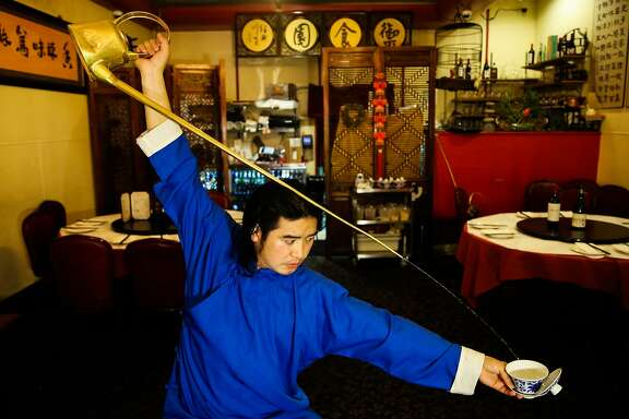 Xiumin Liu pours tea while performing a piece for the San Francisco Chronicle at Z&Y restaurant in San Francisco, California, on Tuesday, Jan. 16, 2018. He is a master of two traditional Sichuan arts: gongfu tea, poured from a copper kettle with a three-foot spout, and �face changing.� He is performing at two Sichuan restaurants in San Francisco through March 2018.