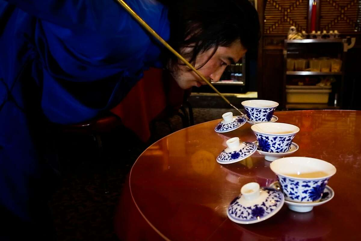 Xiumin Liu pours tea during a performance for the San Francisco Chronicle at Z&Y restaurant in San Francisco, California, on Tuesday, Jan. 16, 2018. He is a master of two traditional Sichuan arts: gongfu tea, poured from a copper kettle with a three-foot spout, and �face changing.� He is performing at two Sichuan restaurants in San Francisco through March 2018.
