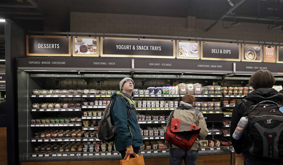 A customer looks overhead in an Amazon Go store, where sensors and cameras are part of a system used to tell what people have purchased and charge their Amazon account, Monday, Jan. 22, 2018, in Seattle. More than a year after it introduced the concept, Amazon opened its artificial intelligence-powered Amazon Go store in downtown Seattle on Monday. (AP Photo/Elaine Thompson)