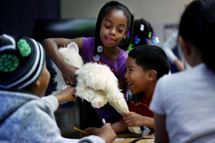 From center left: Jirunyee Hart and William Kenion play with the robotic cat named Michael Jackson at Loma Vista Elementary School, Friday, Jan. 12, 2018, in Vallejo, Calif.