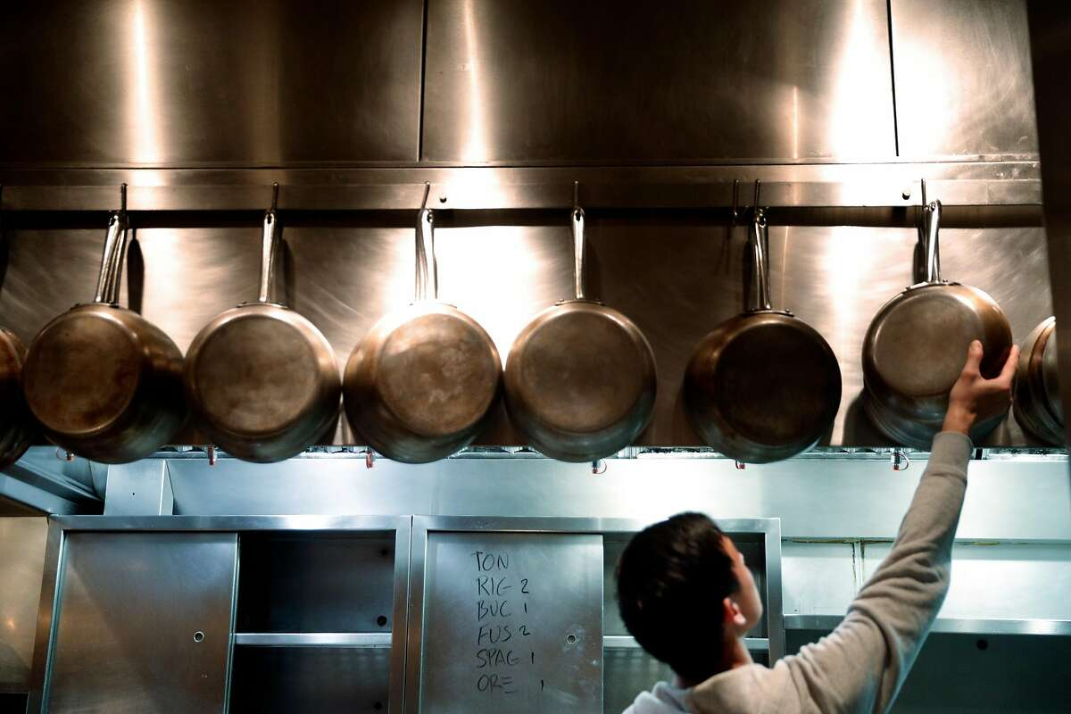 Sous Chef Bryan Hu places cleaned pans back on the hooks after the dinner shift at Locanda in San Francisco, Calif., on Wednesday, January 17, 2018.