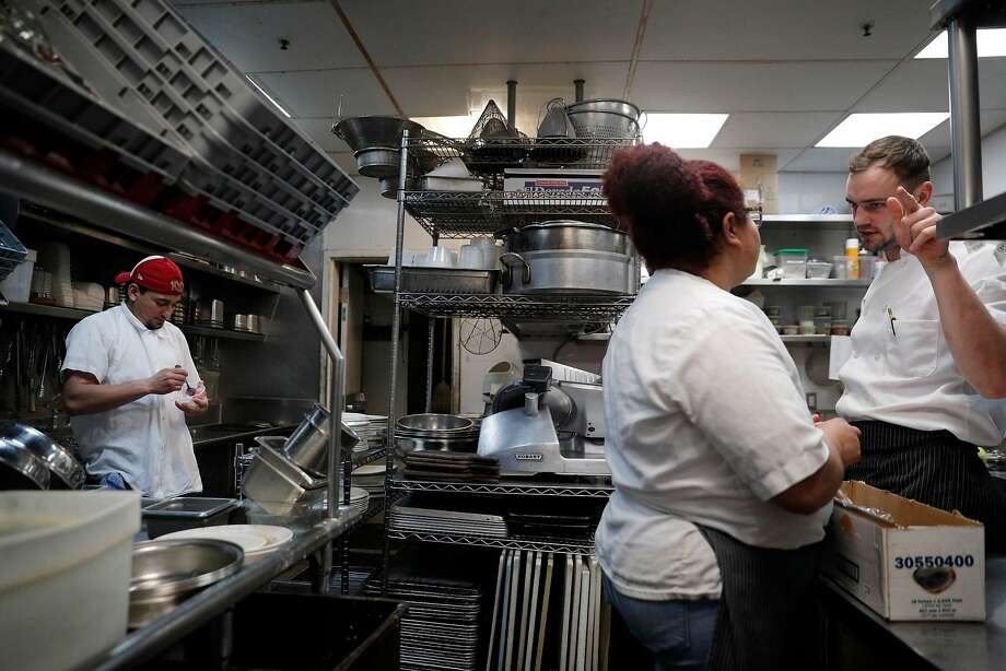 Head dishwasher Carlos Mejia (far left) pauses to eat a bowl of ice cream as cooks Yeni Reyes (center) and Alex LaCasse talk about closing down after the dinner shift at Locanda. Photo: Carlos Avila Gonzalez, The Chronicle
