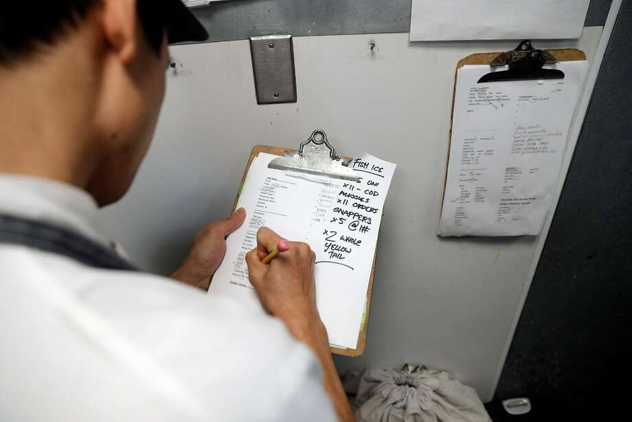 Sous chef Bryan Hu places a clipboard with notes detailing each kitchen station's needs on the hooks in the kitchen for the morning prep crew. Photo: Carlos Avila Gonzalez, The Chronicle
