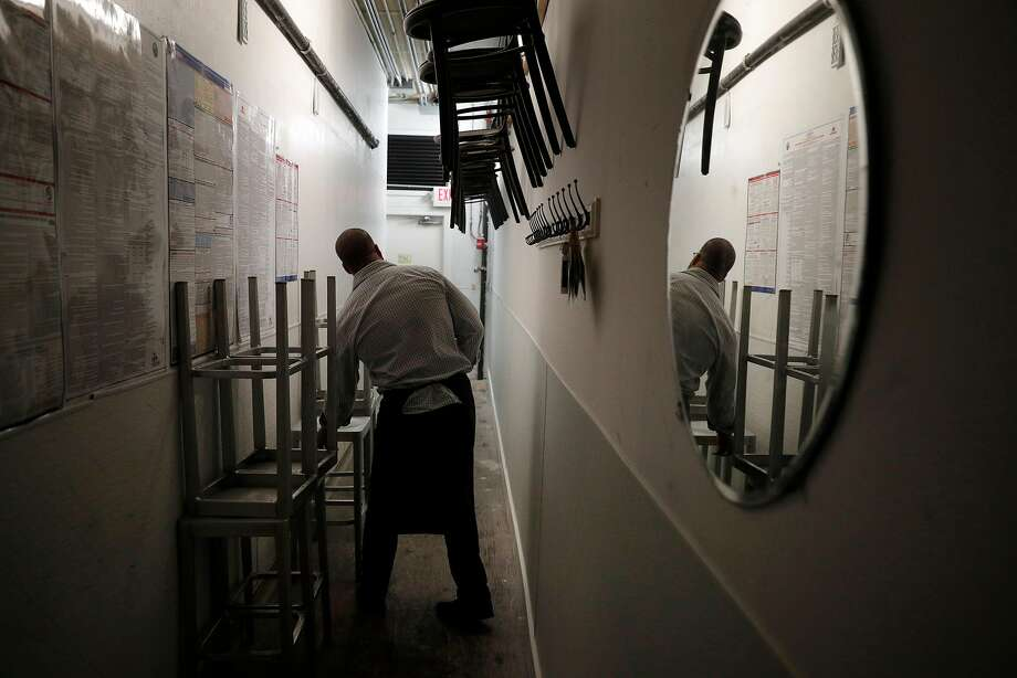 Server Justin Gaines places extra barstools and chairs in a hallway after the dinner shift at Locanda. Photo: Carlos Avila Gonzalez, The Chronicle