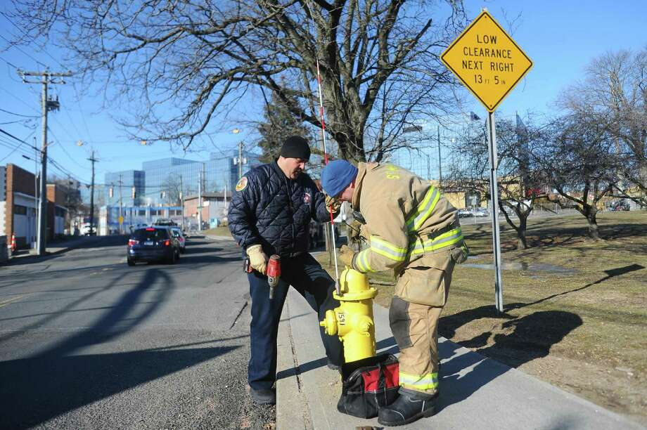 Firefighters Dan Isidro, left, and Ryan Szirmay install a reflective marker on a hydrant at the corner of Greenwich Avenue and Pulaski Street in Stamford, Conn. on Thursday, Jan. 18, 2018. Adding reflective markers on hydrants is the last agreement in the city's settlement over the fatal Christmas 2011 fire that has been completed. Photo: Michael Cummo / Hearst Connecticut Media / Stamford Advocate