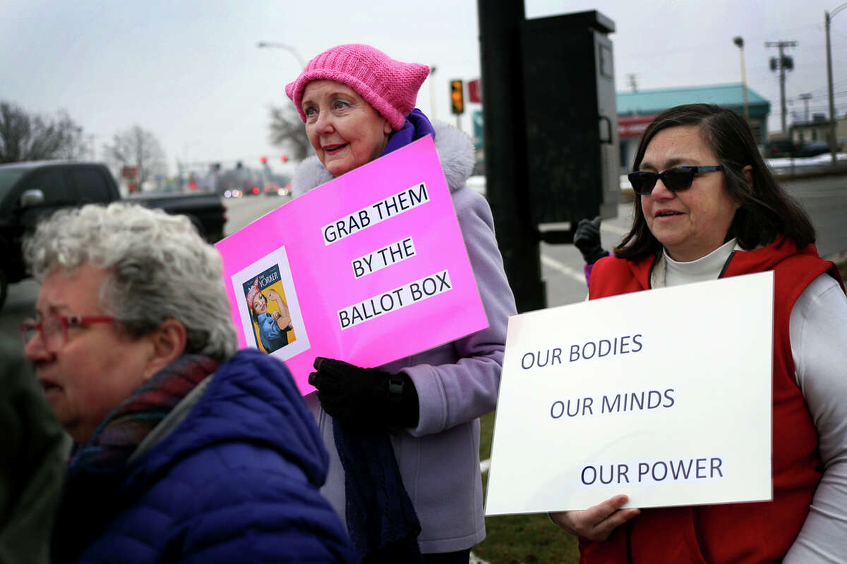 Carol Buller, center, of Midland, marches near the intersection of Washington and South Saginaw during the worldwide Women's March protest on Sunday, Jan. 21, 2018. (Samantha Madar/for the Daily News)
