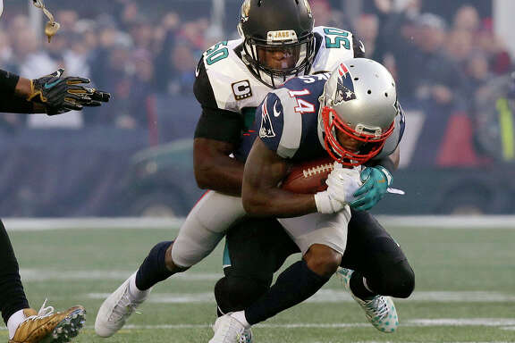 Jacksonville Jaguars linebacker Telvin Smith (50) tackles New England Patriots wide receiver Brandin Cooks (14) during the first half of the AFC championship NFL football game, Sunday, Jan. 21, 2018, in Foxborough, Mass. (AP Photo/Charles Krupa)