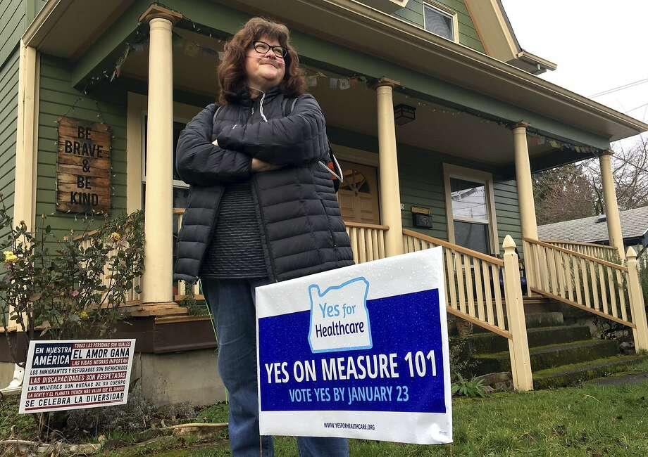 Kelly Burke stands outside her Portland home next to a sign supporting Oregon's Measure 101. The tax would help fund state health care costs. Photo: Gillian Flaccus, Associated Press