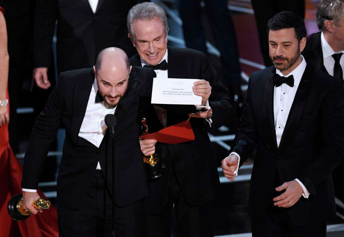 """FILE - In this Feb. 26, 2017, file photo, Jordan Horowitz, producer of """"La La Land,"""" left, shows the envelope revealing """"Moonlight"""" as the true winner of best picture at the Oscars in Los Angeles as presenter Warren Beatty and host Jimmy Kimmel, right, look on. The film academy and its accounting firm, PwC, are announcing a spate of new rules Monday, Jan. 22, 2018, meant to avoid an envelope gaffe like at last year?'s show, when ?""""La La Land?"""" was mistakenly announced as the winner instead of ?""""Moonlight.?"""" PwC U.S. Chairman Tim Ryan said the new protocols include additional personnel and oversight, as well as practicing what to do if a presenter reads the wrong name. (Photo by Chris Pizzello/Invision/AP, File)"""