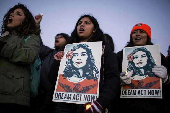 "Demonstrators sing and hold signs during a rally supporting the Deferred Action for Childhood Arrivals program (DACA), or the Dream Act, outside the U.S. Capitol building on Thursday. The president's comments about ""s-thole"" countries inflamed matters."