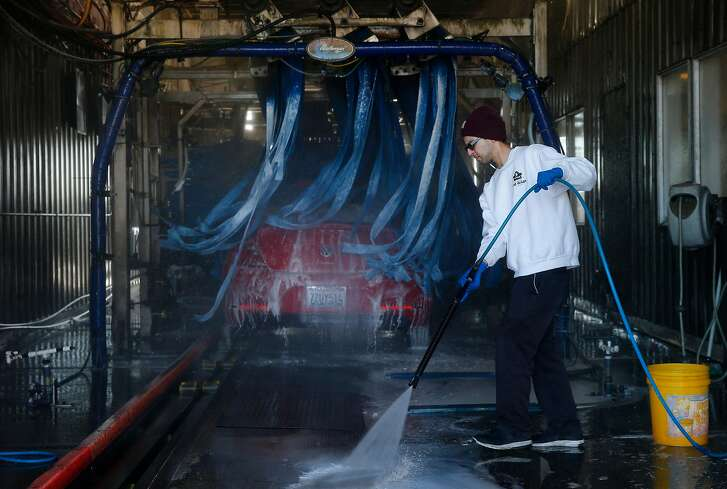 Cole Gomez cleans the area after washing a car at the 5 Star Car Wash and Detail Center, Saturday, Jan. 20, 2018, in Fairfield, Calif.