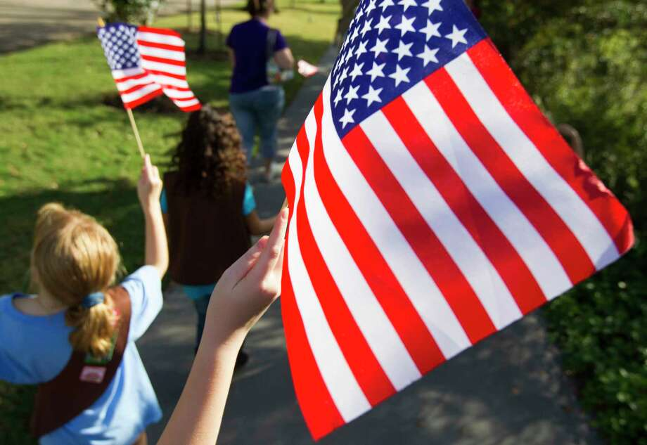 """Kids proudly wave their American Flags as they participate in American Election Day events at Bayou Bend in Houston on Nov. 4, 2012. The event was designed to teach the American democratic process to youngsters with historic re-creations, including a live 19th-century-style debate, re-enactors, and a chance to practice voting using the """"bean & corn"""" method that was common in the early days of the country.  (For the Houston Chronicle) Photo: J. Patric Schneider, Freelance / © 2012 Houston Chronicle"""