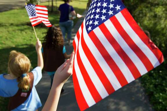 "Kids proudly wave their American Flags as they participate in American Election Day events at Bayou Bend in Houston on Nov. 4, 2012. The event was designed to teach the American democratic process to youngsters with historic re-creations, including a live 19th-century-style debate, re-enactors, and a chance to practice voting using the ""bean & corn"" method that was common in the early days of the country.  (For the Houston Chronicle)"