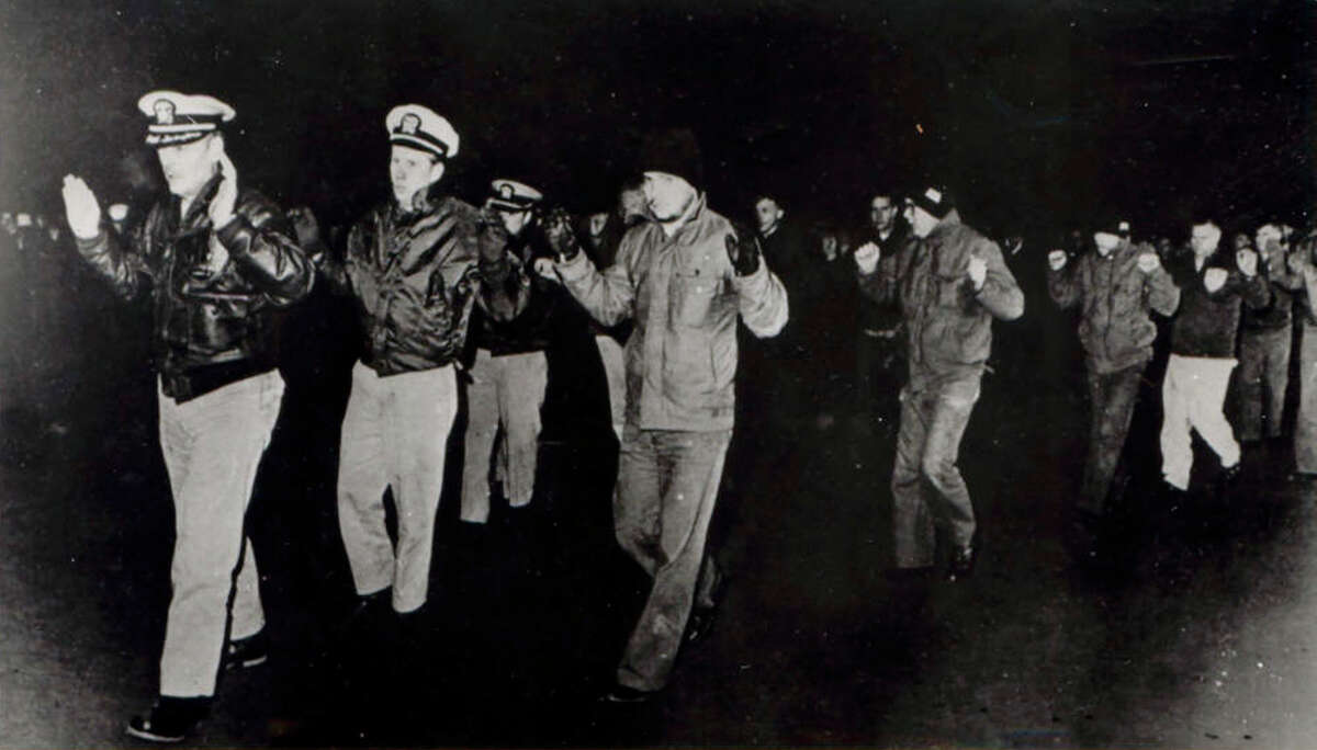 """FILE - In this photo released by the U.S. Navy, crew members of the USS Pueblo hold up their hands while in captivity in North Korea in 1968. Many of the crew who served on the vessel, then spent 11 months in captivity in North Korea, want to bring the Pueblo home. Throughout its history, they argue, the NavyÂ?'s motto has been Â?""""donÂ?'t give up the ship.Â?"""" The Pueblo, in fact, is still listed as a commissioned U.S. Navy vessel, the only one being held by a foreign nation. (AP Photo/US Navy)"""