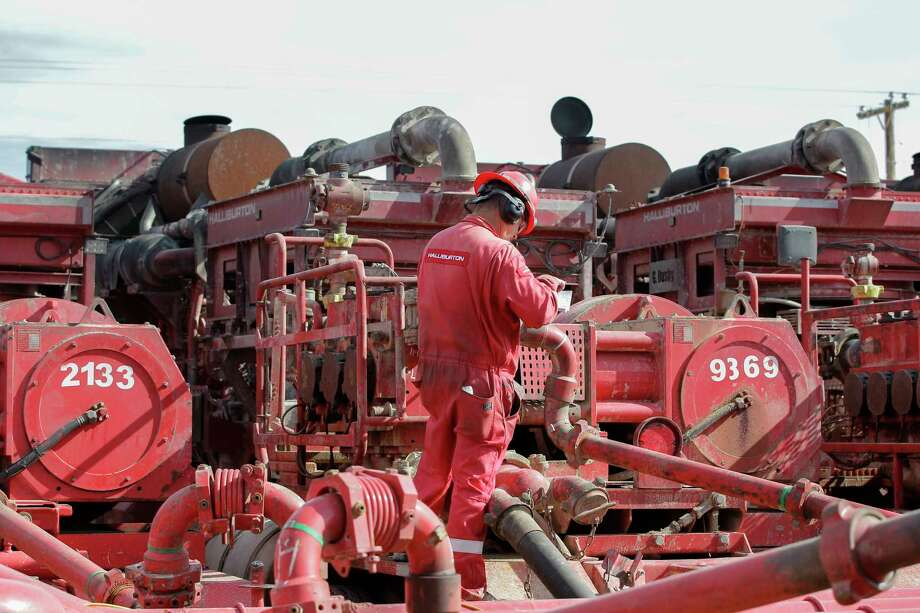 FILE - In a Monday, June 26, 2017, file photo, a Halliburton employee works near rows of hydraulic fracturing pumping units at a three pad site in Midland, Texas. Halliburton Co. reports earnings, Monday, Jan. 22, 2018. (Steve Gonzales//Houston Chronicle via AP, File) Photo: Steve Gonzales, MBO / © 2017 Houston Chronicle