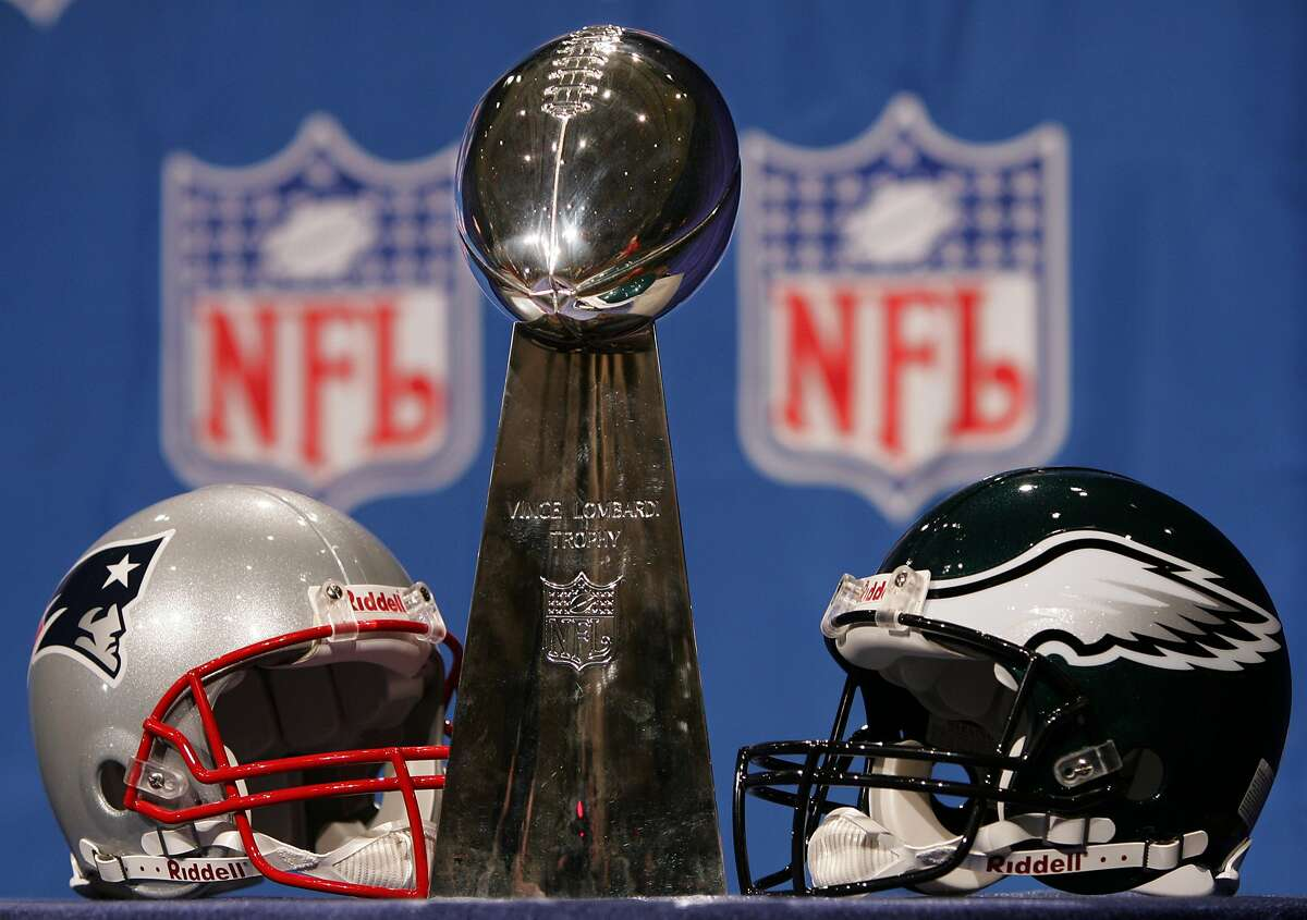 The Vince Lombardi Trophy sits on display with the New England Patriots and Philadelphia Eagles helmets at the Prime F. Osborn Convention Center in Jacksonville, Fla., Friday, Feb. 4, 2005.