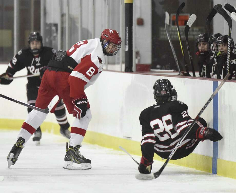 Greenwich's Alex Mozian checks New Canaan's Shane Pickering into the boards on Monday evening at Dorothy Hamill Rink in Greenwich Photo: Tyler Sizemore / Hearst Connecticut Media / Greenwich Time